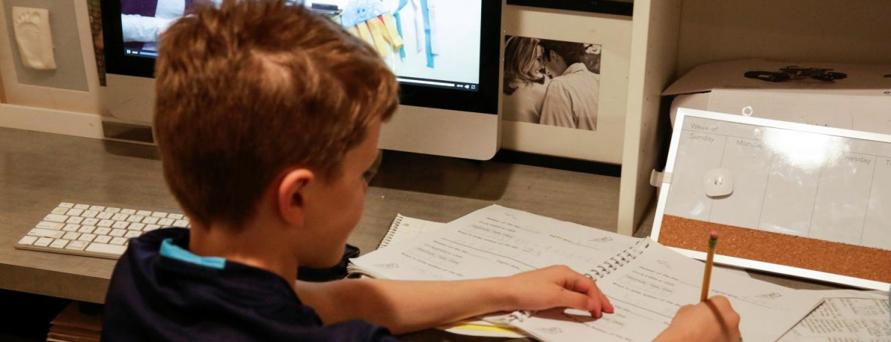 """Oakes McClenahan, 7, does his school work as he watches his teacher's recorded lesson on a computer at home during Washington Governor's """"stay home, stay healthy"""" initiative as efforts continue to help slow the spread of coronavirus disease (COVID-19) in Seattle, Washington, U.S. March 27, 2020.  REUTERS/Jason Redmond - RC2LSF988R5B"""